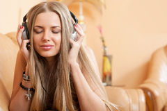 Young attractive girl enjoying music through headphones, lying o Stock Photos