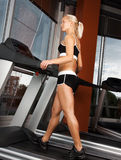 Young attractive girl exercise on treadmill. Portrait of young attractive athlete doing exercise on treadmill Stock Images