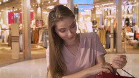 Young attractive girl goes shopping in mall, watches in bags, express surprise, smile, shopping concept, fashion concept.  stock video
