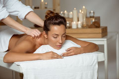 Young attractive girl having massage relaxing in spa salon. Stock Image