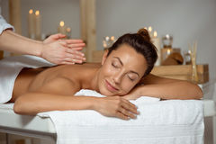 Young attractive girl having massage relaxing in spa salon. Stock Images
