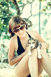 Young attractive girl with her pet dog Beagle at the beach of tropical island Bali, Indonesia. Happy moments. Royalty Free Stock Photo