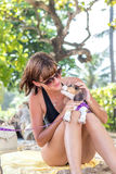 Young attractive girl with her pet dog Beagle at the beach of tropical island Bali, Indonesia. Happy moments. Royalty Free Stock Photography
