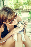 Young attractive girl with her pet dog Beagle at the beach of tropical island Bali, Indonesia. Happy moments. Stock Photos