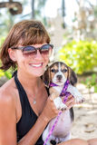 Young attractive girl with her pet dog Beagle at the beach of tropical island Bali, Indonesia. Happy moments. Royalty Free Stock Photos