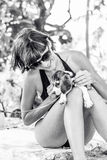 Young attractive girl with her pet dog Beagle at the beach of tropical island Bali, Indonesia. Happy moments. Black and Stock Photos