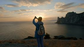 Young attractive girl hiking makes photo on smartphone. Shoots a beautiful sunset on a cape by the sea. Reached the goal