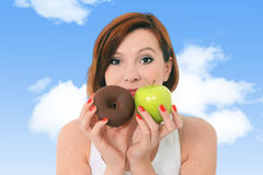 Young attractive girl holding apple and chocolate donut in fitne Royalty Free Stock Image