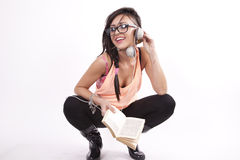 Young attractive girl holding a book. Young beautiful cool girl with headphones holding a book and listening music Royalty Free Stock Photos