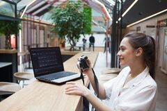 Free Young Attractive Girl Is Sitting In Front Of A Laptop And Holding A Camera In Her Hands. Photographer And Retoucher Royalty Free Stock Photos - 180521488