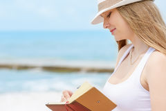 Young attractive girl with kind smile is writing some idea or letter in her note book by pen on background of blue sea. At sunny summer day Stock Photo