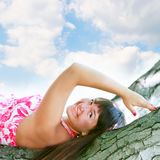 Young attractive girl laying on tree Stock Image