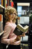 Young attractive girl in a library Royalty Free Stock Image