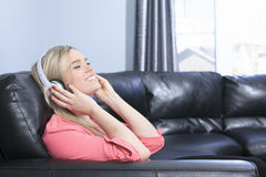 Young attractive girl listening to the music in. A Young attractive girl listening to the music in modern interior Royalty Free Stock Image