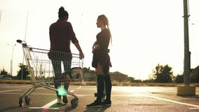 Young attractive girl in long socks is holding a skateboard and talking to her girlfriend that is sitting on the. Shopping cart in the parking near the shopping stock footage