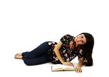 Young attractive girl lying and reading book Stock Images