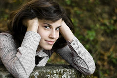 Young attractive girl lying on a wall. Young attractive girl lying on a concrete wall in the park Stock Image
