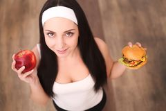 Young attractive girl making choice between healthy and harmful food.  Stock Photography
