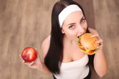 Young attractive girl making choice between healthy and harmful food Stock Images