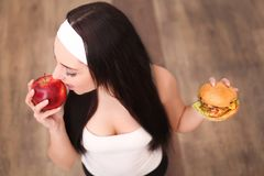 Young attractive girl making choice between healthy and harmful food Stock Photo