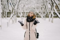 Young attractive girl in nerd glasses, a beige down jacket and knitted hat with a pompon smiles and fools around stock photo