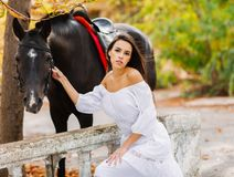 Attractive girl next to a horse. Outside. In the autumn park. Stock Photo