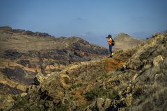 Young and attractive girl in orange shirt and blue leggings is hiking by the tourist`s trail. Young and attractive girl in orange shirt and blue leggings is stock photos