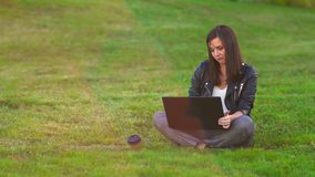 A young attractive girl in a Park on the lawn dreams and writes a story about herself on a laptop. stock video