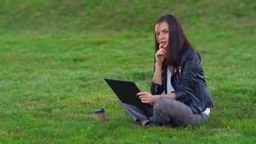 A young attractive girl in a Park on the lawn dreams and writes a story about herself on a laptop. stock footage