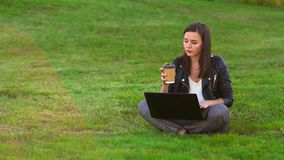 Young attractive girl in the Park on the lawn working with a laptop. Drink coffee. stock video