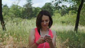 Young attractive girl in pink shirt with headphones listening music on smartphone. Sportive brunette girl dancing in park. Slim cu. Te woman turns on music on stock video