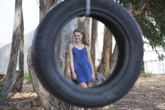 A young attractive girl playing with a tyre swing. In the woods Stock Images