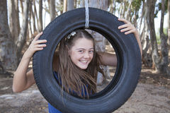 A young attractive girl playing with a tyre swing Stock Photo