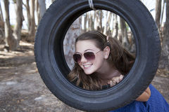 A young attractive girl playing with a tyre swing. In the woods Stock Photos