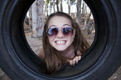 A young attractive girl playing with a tyre swing. In the woods Stock Image