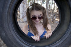 A young attractive girl playing with a tyre swing. In the woods Royalty Free Stock Photography