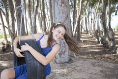 A young attractive girl playing with a tyre swing