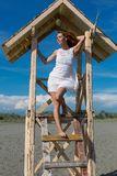 Young attractive girl posing on a lifeguard tower Royalty Free Stock Image