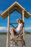Young attractive girl posing on a lifeguard tower Royalty Free Stock Photography