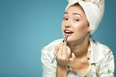 Young attractive girl putting lipstick on lips over blue, beauty Stock Photos