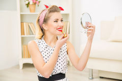 Young attractive girl putting lipstick on. Refreshing make up. Young beautiful woman is smiling while applying red bright lipstick on royalty free stock image
