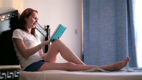 Young attractive girl reading a book, smiling stock footage