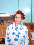 The young attractive girl with red hair in a dressing gown and with wound hair curlers costs in kitchen and smiles. Stock Image