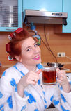 The young attractive girl with red hair about hair curlers has tea in kitchen Royalty Free Stock Images
