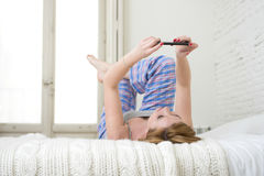 Young attractive girl with red hair internet networking with mobile phone lying on bed in sleeping pants Stock Photography