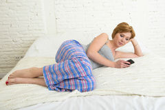 Young attractive girl with red hair internet networking with mobile phone lying on bed in sleeping pants Royalty Free Stock Photos