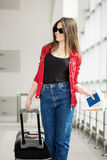 Young attractive girl in a red jacket with a suitcase goes on the terminal. In all growth Royalty Free Stock Photo