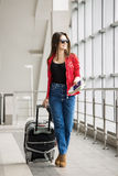 Young attractive girl in a red jacket with a suitcase goes on the terminal. In all growth Stock Photography
