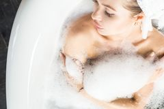 A young attractive girl relaxes in the bathroom and rests against the backdrop of a beautiful light interior. Spa stock photography