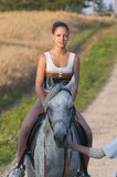 Young attractive girl rides a horse Royalty Free Stock Image